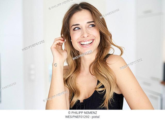 Happy young woman wearing black dress looking sideways