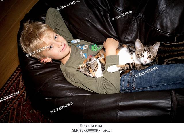 Boy relaxing with cat on couch