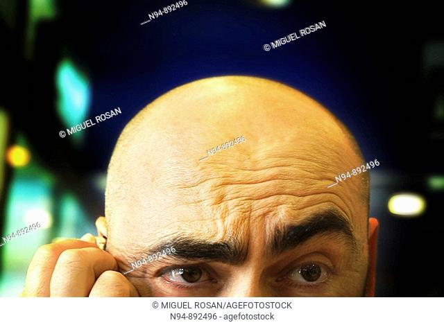 Young man, bald with a thoughtful gesture