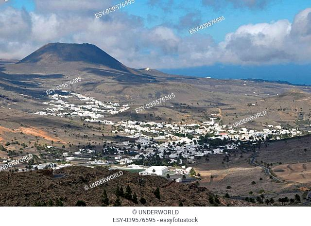 Small town in the desert near a volcan on a cloudy sky