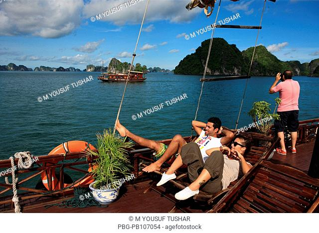 Tourists travelling on boat at Halong Bay It is located in Quáng Ninh province, Vietnam The bay features thousands of limestone karsts and isles in various...