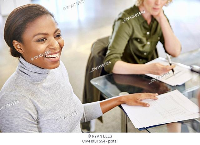 Smiling businesswoman with paperwork in meeting