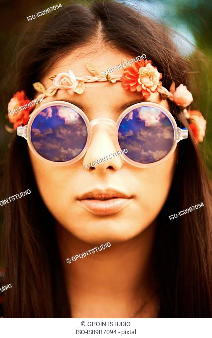 Portrait of young hippy woman in floral headband and sunglasses at festival