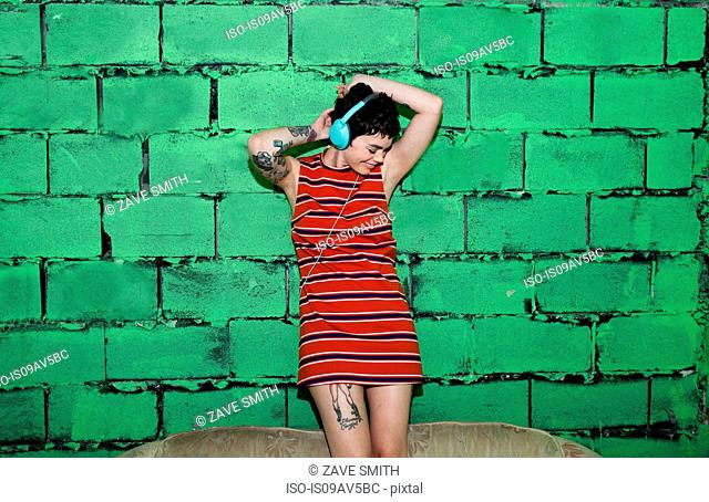 Mid adult woman with tattoos, wearing headphones, dancing