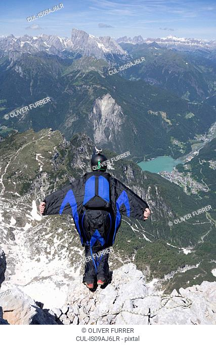 Mid adult man BASE jumping from mountain edge, Alleghe, Dolomites, Italy