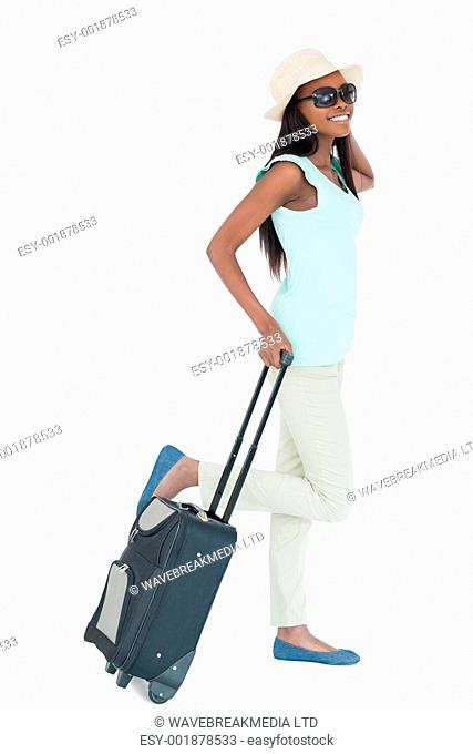 Happy young woman with her suitcase against a white background