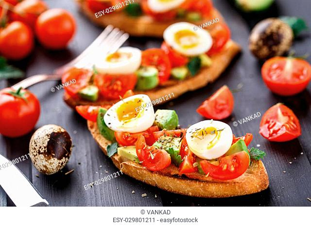 Bruschetta with tomato, avocado and quail egg on a wooden table