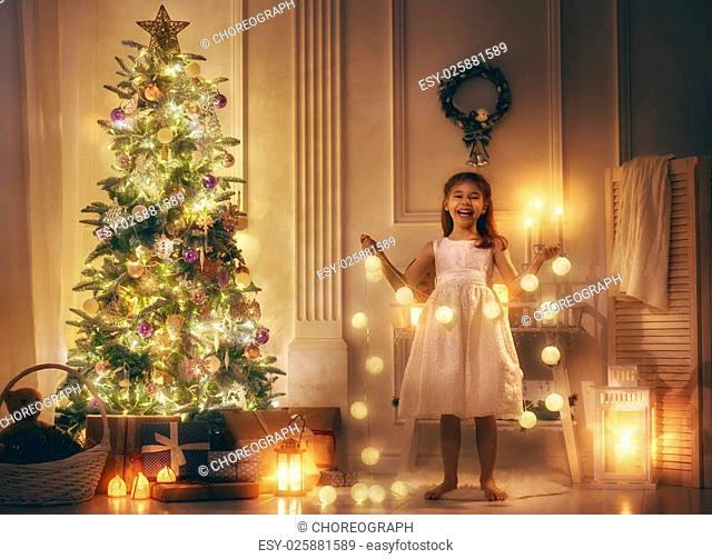 Merry Christmas! Cute little child girl is decorating the Christmas tree