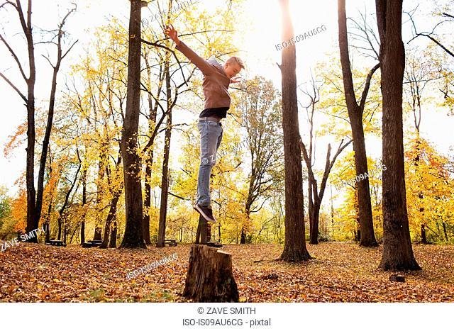 Teenage boy jumping on tree stump in autumn forest