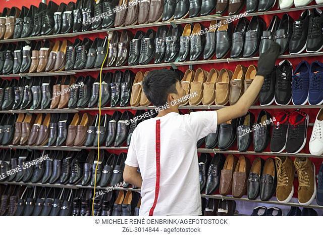 Local flea market boy shining shoes for sale in Sapa Vietnam