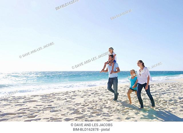 Caucasian parents and children walking on beach