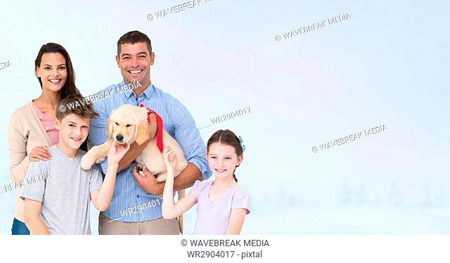 Portrait of happy family with dog against gray background