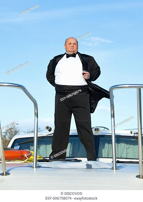 Overweight man in tuxedo standing on the deck of a luxury pleasure boat with glass red wine