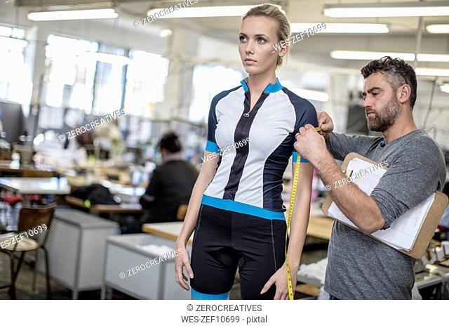 Tailor measuring arm of model wearing sportswear