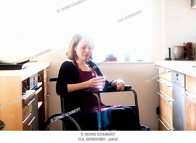 Woman in wheelchair with glass of water in kitchen