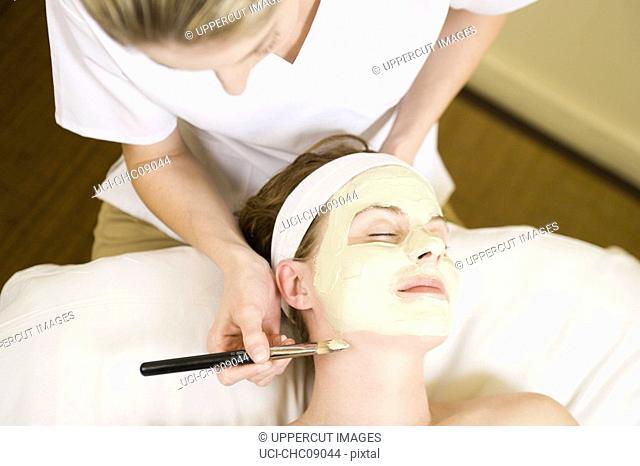 Woman receiving facial spa treatment