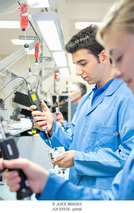 Technicians using electric screwdrivers to assemble machine parts on production line in manufacturing plant