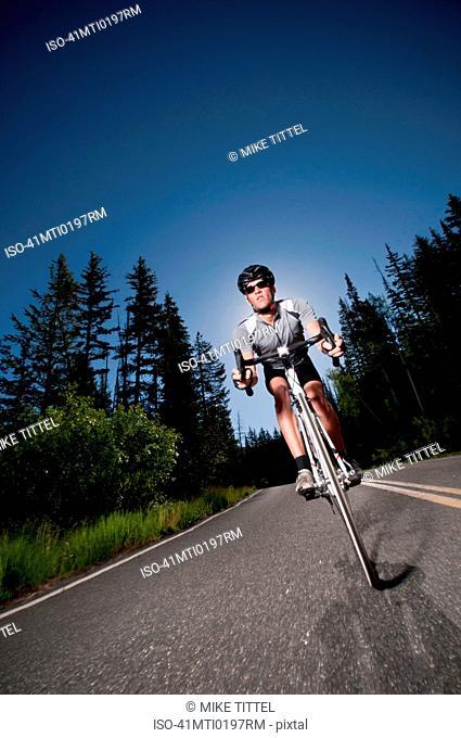Cyclist biking on rural road