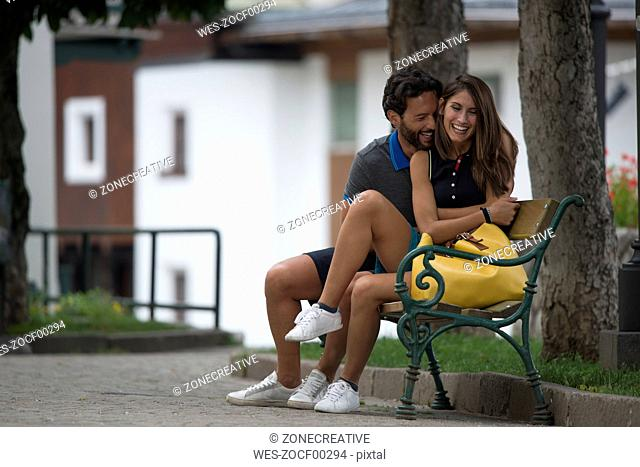 Happy couple sitting on bench in a town