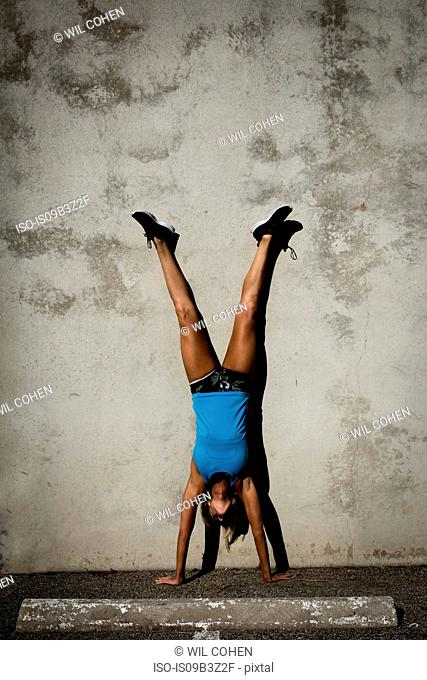 Athlete doing handstand against wall