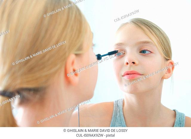 Over the shoulder mirror image of girl applying mascara