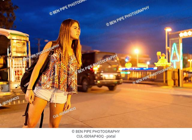 Young woman looking out from street at night, Tagbilaran, Bohol Province, Philippines