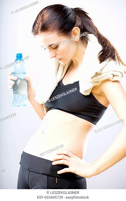 Young woman looking at her flat stomach with towel and water bottle
