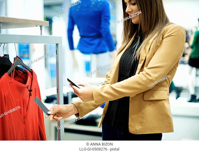 Smiling woman scanning QR code on smart phone Debica, Poland