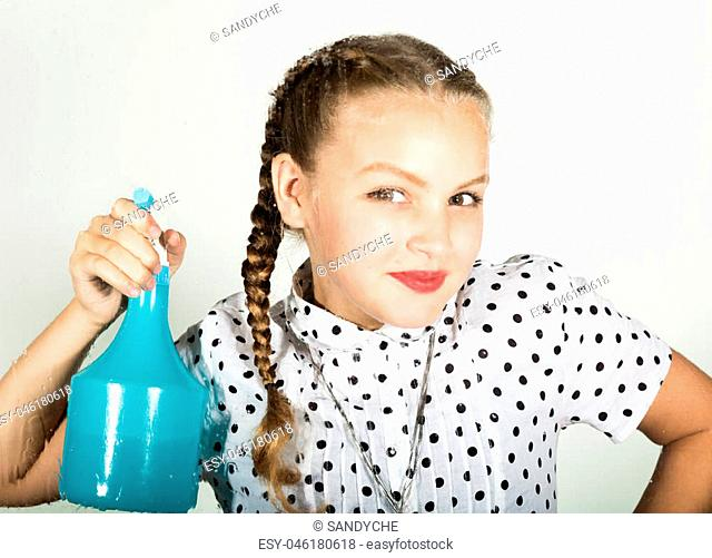 Smiling little housewife washed the window with a cloth and detergent. Large window glass in foam. Housework concept