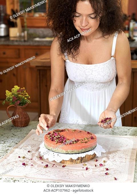 Pretty young woman decorating a homemade strawberry cake with rose buds and pumpkin seeds in the kitchen at home