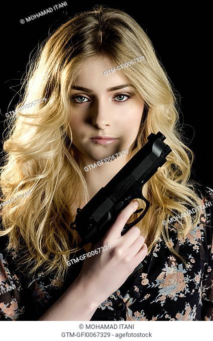 Beautiful young woman holding a gun