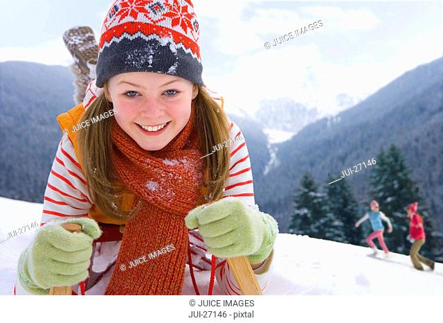 Close up of girl laying on sled on ski slope