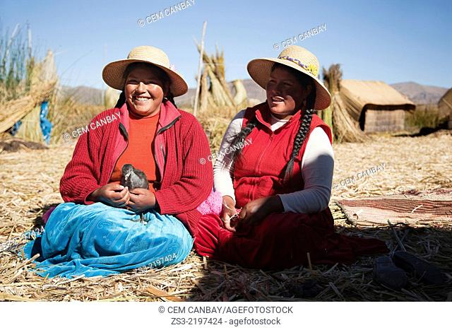Young Aymara women feeding animal at Uros Islands, Lake Titicaca, Puno Region, Peru, South America