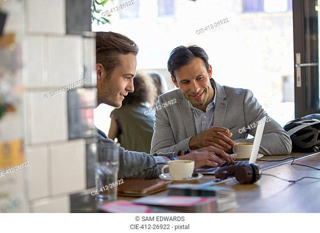 Businessmen with coffee working at laptop in cafe