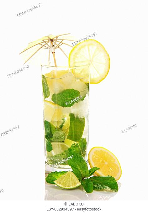 The glass of a cold mojito is decorated with an umbrella, slices of a lemon and mint, are isolated on white