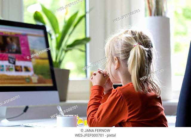 Little girl watching something on computer monitor