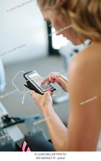 Young woman using mobile while exercising in gym