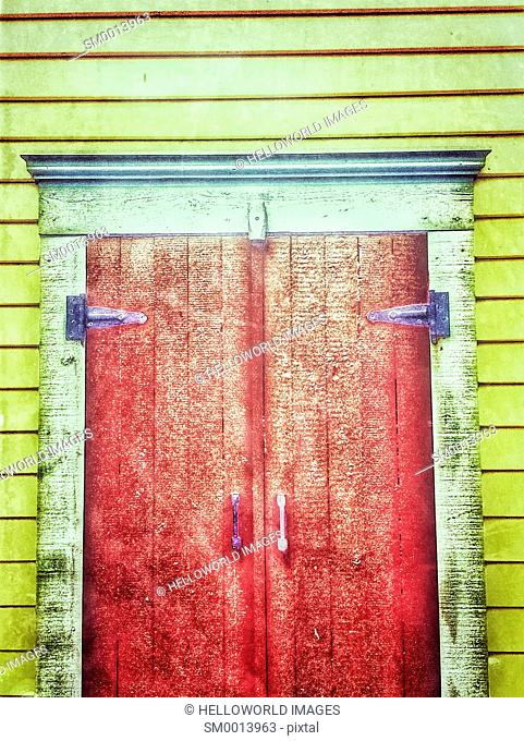 Red timber doors on yellow wooden building