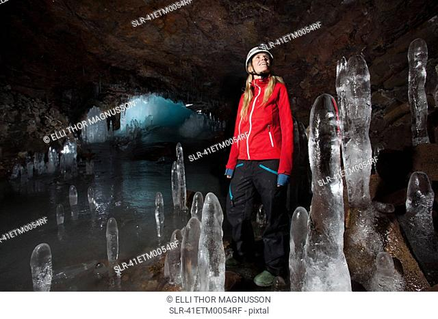 Hiker with stalactites in glacial cave