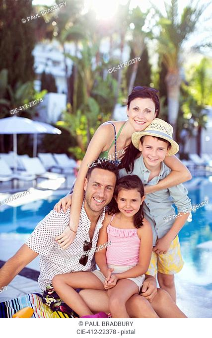 Portrait of happy family by swimming pool