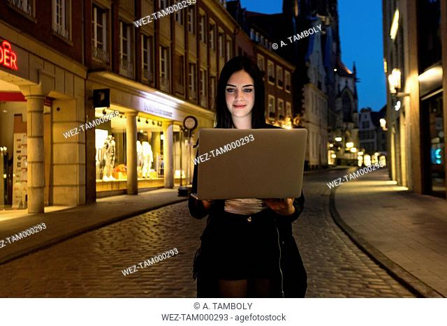 Germany, Muenster, portrait of young woman using laptop in the city at evening