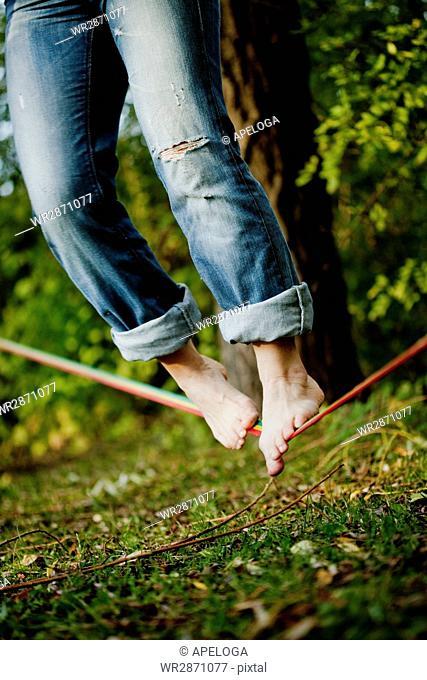 Tilt shot of man balancing on tightrope over grass at park