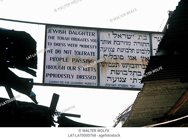 Mea Shearim orthodox Jewish area of city with sign across the road in Hebrew and English advocating modesty in dress for women