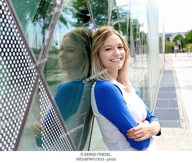 Smiling blond young woman leaning on a glass facade