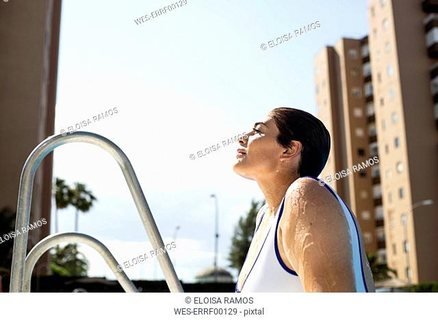 Profile of wet young woman leaving swimming pool