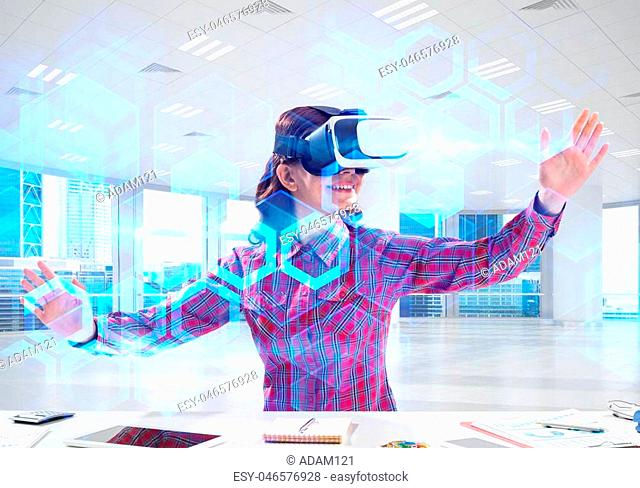 Beautiful and young woman in red checkered shirt using VR goggles and interracting with digital media interface while sitting inside bright office building