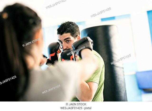 Man abd woman boxing in gym