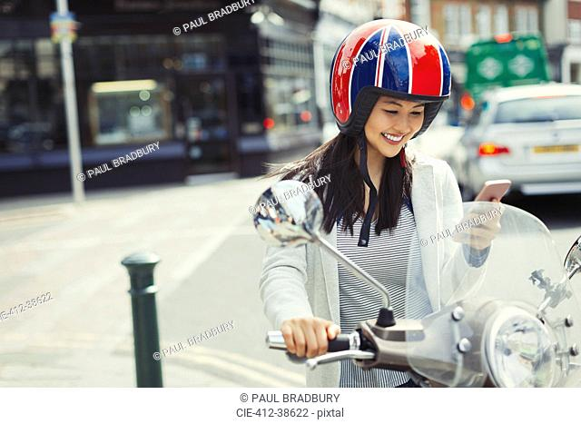 Smiling young woman texting with cell phone on motor scooter, wearing helmet on urban street