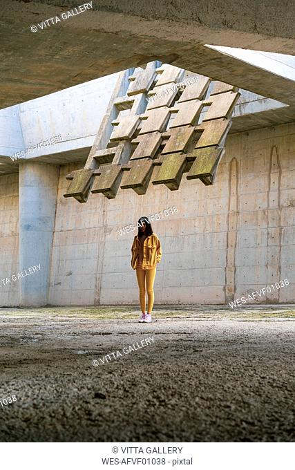 Young woman wearing yellow jeans clothes, standing in concrete building