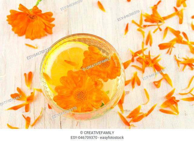 marigold flower herbal tea with lemon slices in a glass